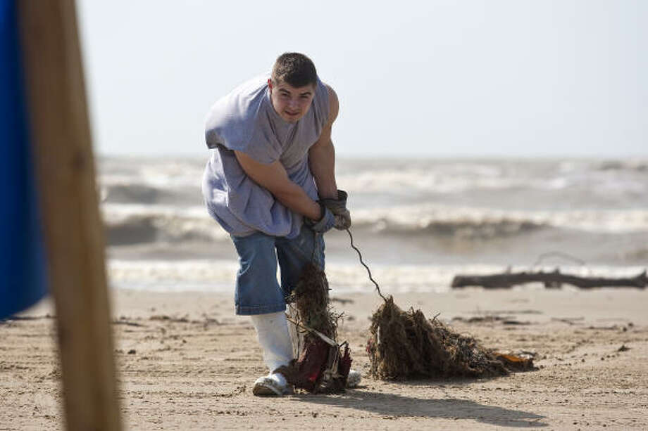Michael Scapuzzo drags a load of debris off the beach Saturday during a cleanup effort at Crystal Beach.  Photo: Todd Spoth, For The Chronicle