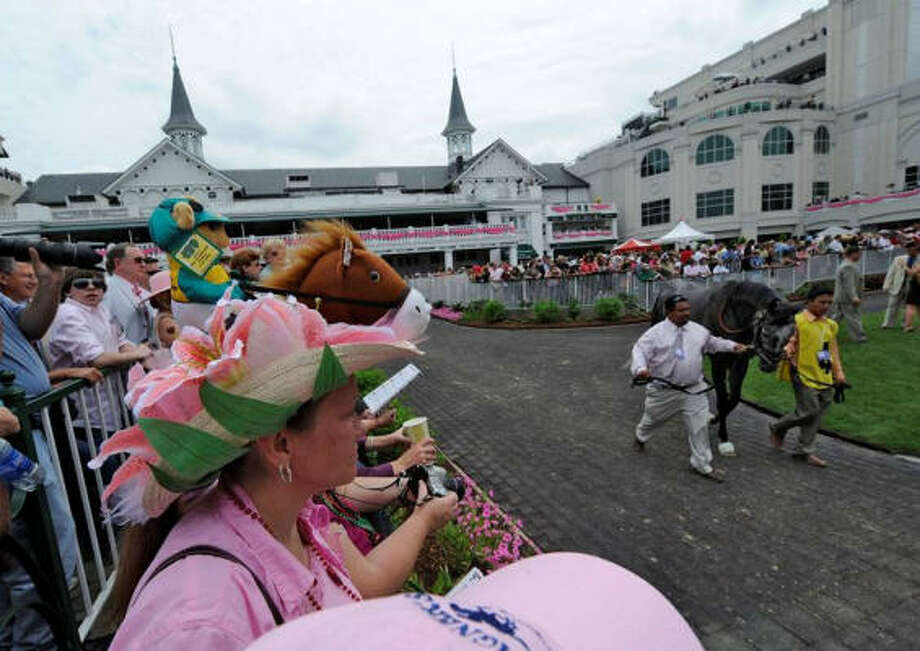 Fans watch the horses arrive Friday against the storied backdrop of Churchill Downs and gathering clouds. Today's forecast is a mudder's dream, with a 70 percent chance of rain. Photo: Skip Dickstein