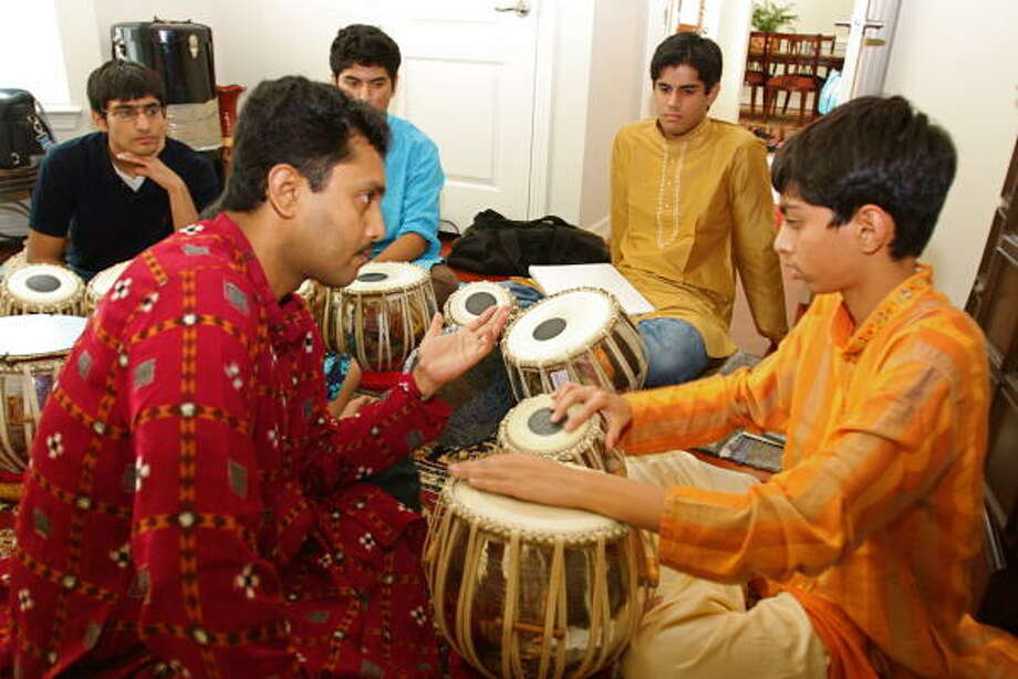 SUZANNE REHAK: FOR THE CHRONICLE THE RIGHT BEAT: Raja Banga teaches lessons on the tabla at his Katy home to Rishabh Shah, 13.  Watching from behind, from left, are Nikhil Garg, 16, of Katy; Nikhil Chaudhury, 16, of Katy; and Parth Vyas, 16, of Katy. Photo: Suzanne Rehak, For The Chronicle
