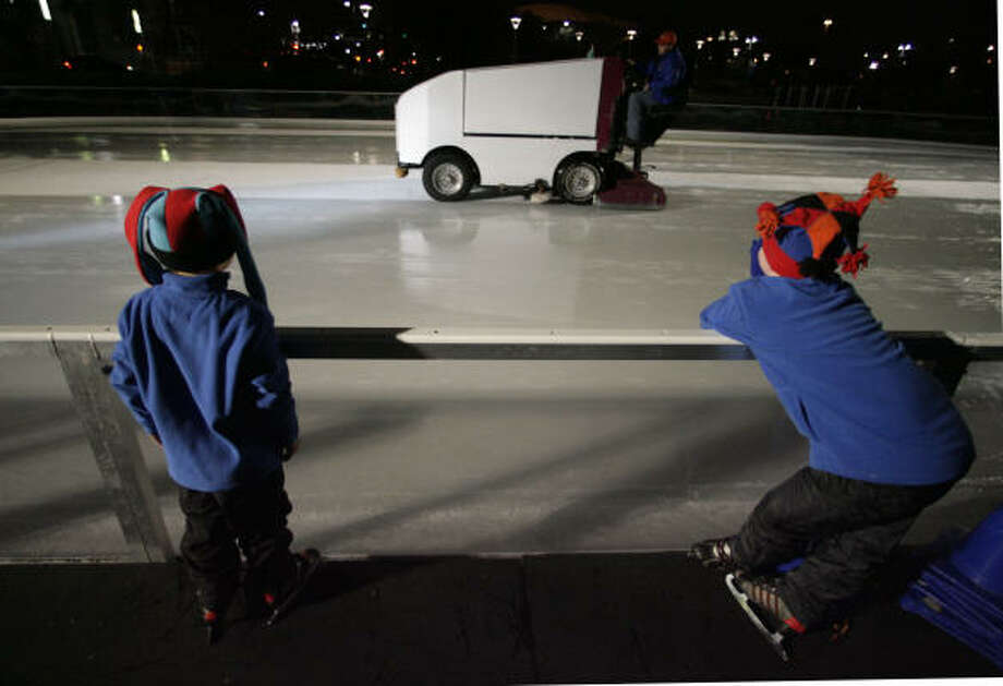 Dylan, left, and Carter Bentson take a break from the ice as the zamboni resurfaces the ice at The Ice at Discovery Green. Photo: BILLY SMITH II :, CHRONICLE
