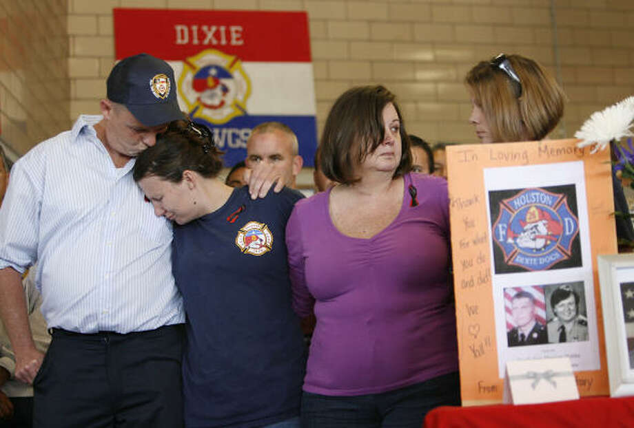 Fallen firefighter James Harlow's family — son, James Harlow Jr.; daughter, Brandy, and wife, Debbie — hold a news conference Tuesday at HPD Fire Station 26. Photo: Mayra Beltran, Chronicle