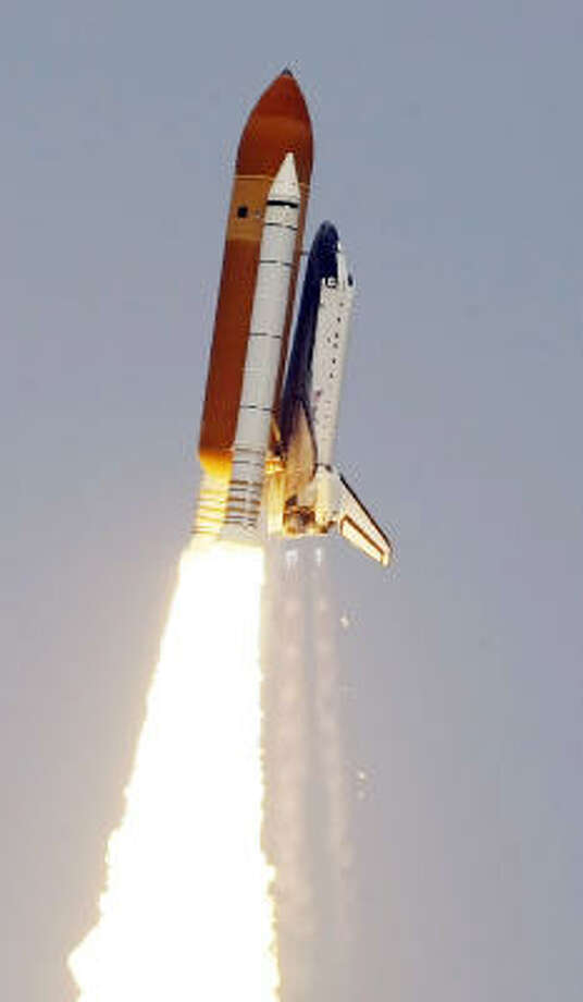 Debris is seen falling from Atlantis after the orbiter's liftoff on Monday.  Photo: Chris O'Meara, AP