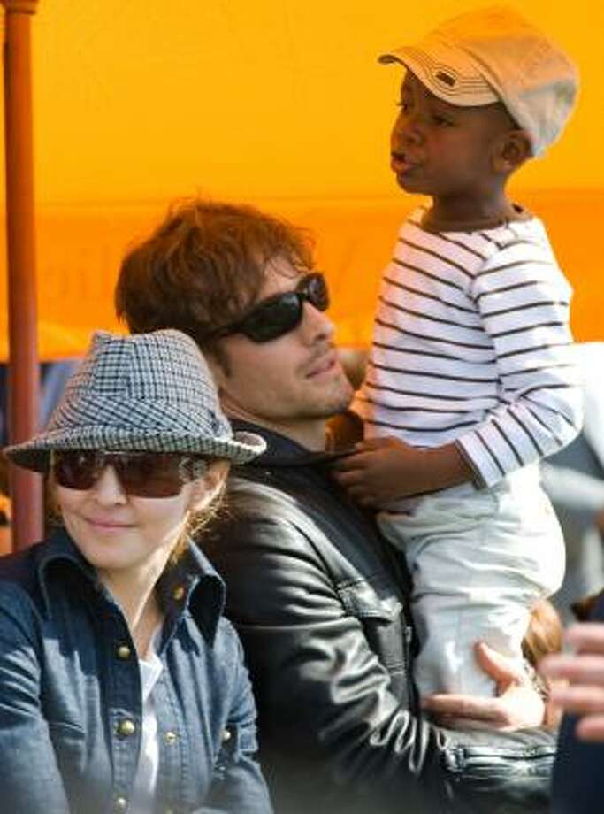 Madonna and her son David Banda, along with photographer Stephen Klein, watch the Veuve Clicquot Manhattan Polo Classic in New York in 2009. Photo: Charles Sykes, Associated Press