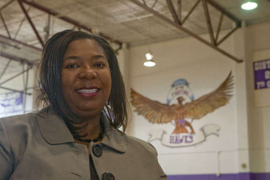 McAuliffe Middle School Principal Sharon Delesbore stands in front of the Fighting Hawk mural in the boys' gymnasium. Photo: R. Clayton McKee, For The Chronicle