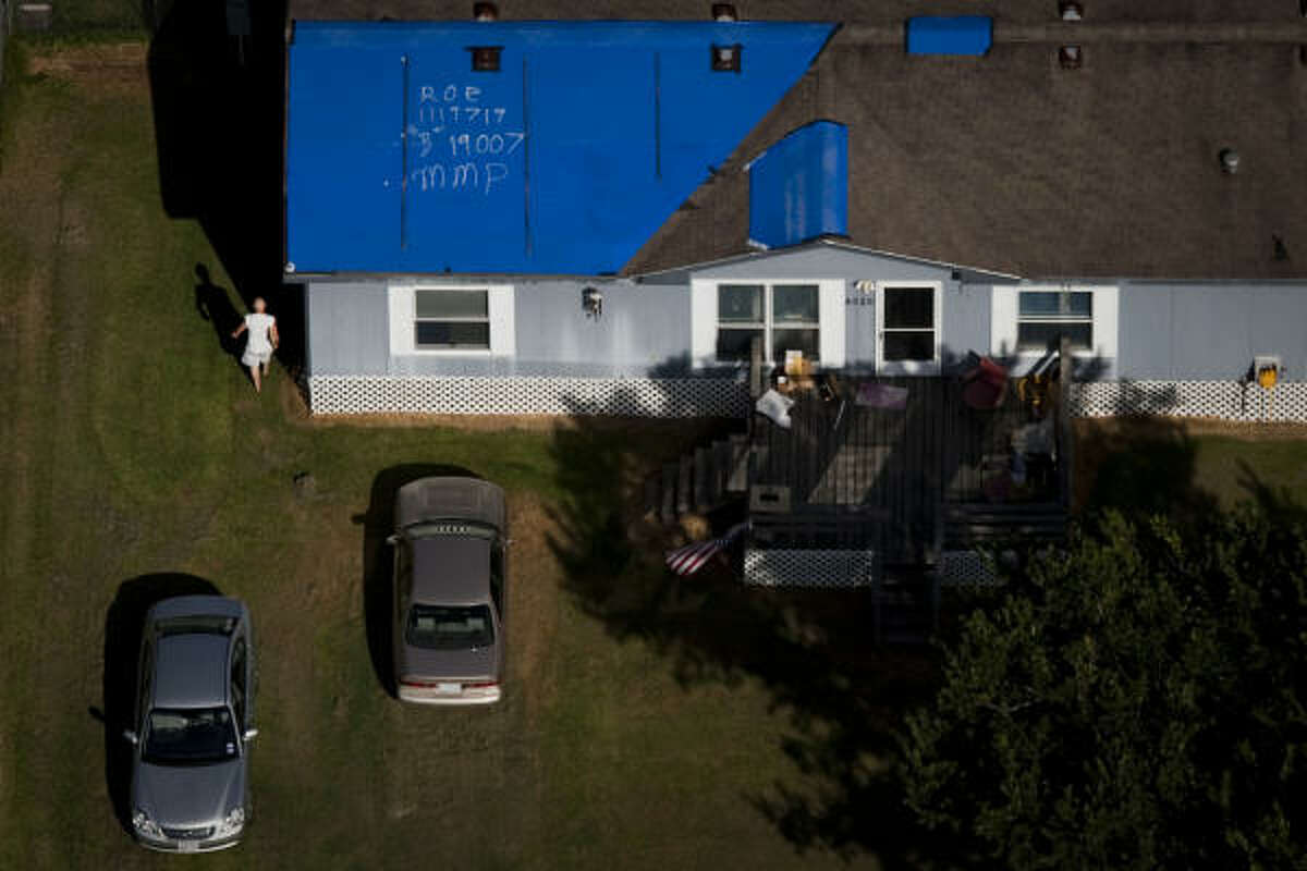 A storm-damaged house near Santa Fe still has a blue tarp on its roof nearly a year after Hurricane Ike.