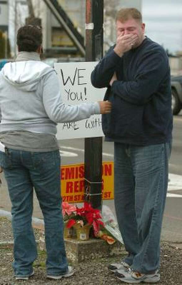 Glenn Carlson of Tacoma reacts at a makeshift memorial near the site where four police officers were killed in an ambush at the Forza Coffee company in Parkland, Wash., on Sunday. Photo: Lui Kit Wong, AP
