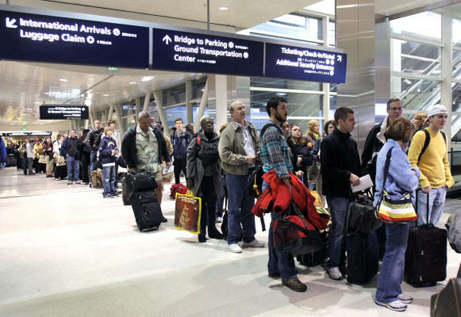 Passengers have a long wait for a security check at Detroit Metropolitan Airport on Saturday, a day after a man allegedly tried to blow up a plane as it approached the city. Photo: Bill Pugliano, Getty Images