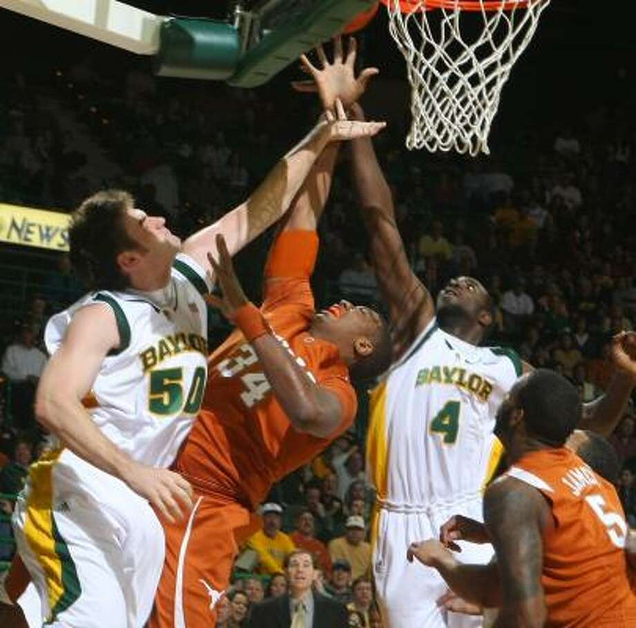 Texas' Dexter Pittman (second from left) scores between two Baylor defenders in the first half of Tuesday's game. Photo: Jerry Larson, AP