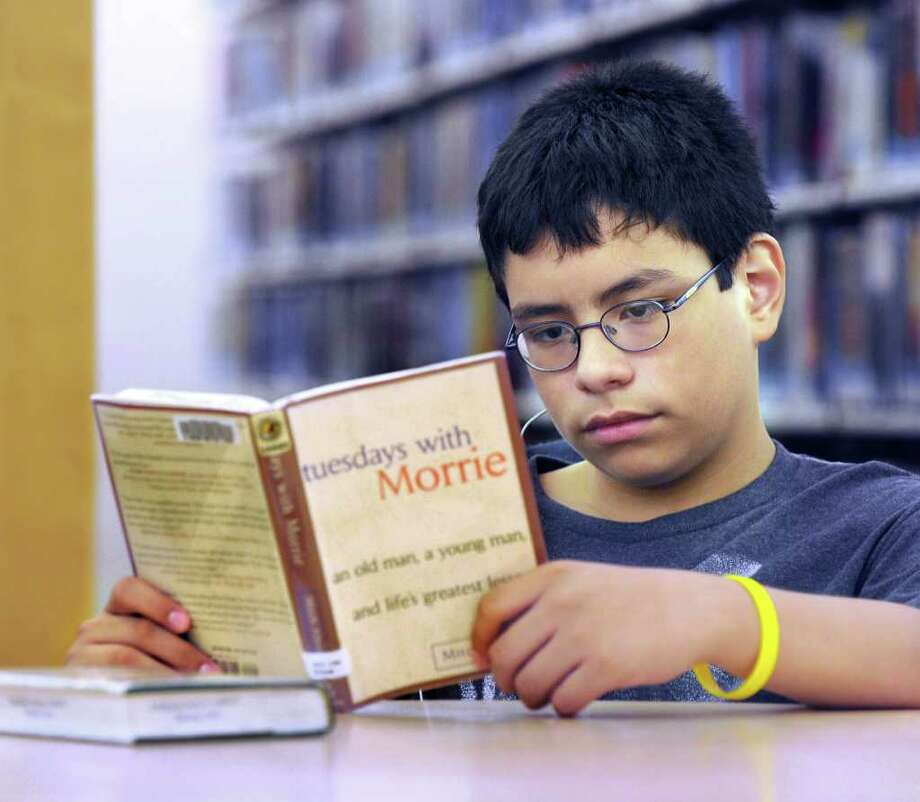 "Oscar Cortez, 13, reads ""Tuesdays with Morey"" at the Danbury Library Friday. He will be a freshman at Danbury High School in September. The book was on the school's summer reading list.  Photo taken Friday, Aug. 5, 2011. Photo: Carol Kaliff / The News-Times"