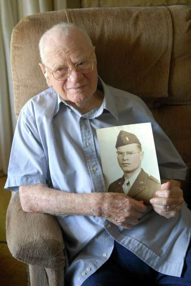 95-year-old Orlando Francesconi of Darien, Conn. with WWll photo of himself before receiving  medal from Congressman Jim Himes for his service during World War II.  Francesconi, who was born in Stamford, was a second lieutenant during the war and saw service in North Africa and Sicily. He and his wife of 64 years, Nancy LoCicero Francesconi (originally from Stamford), live in the house they built in Darien in 1947. Photo: Dru Nadler / Stamford Advocate Freelance