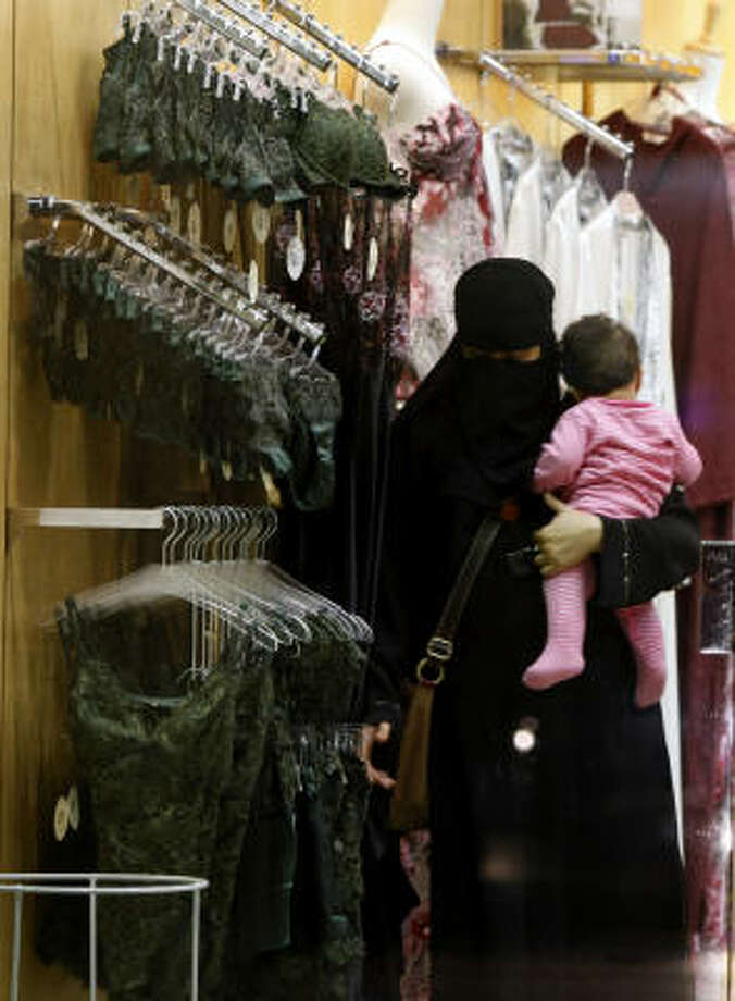 A woman checks out lingerie at a store in Riyadh, Saudi Arabia, where fitting rooms are banned. Photo: Hassan Ammar, Associated Press