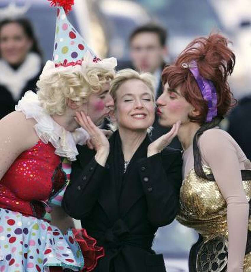 Actress Renee Zellweger is kissed by Hasty Pudding Theatricals actors Tom Compton, left, and Dave Andersson during a parade through the Harvard Square neighborhood of Cambridge, Mass., on Thursday. Photo: Steven Senne, ASSOCIATED PRESS