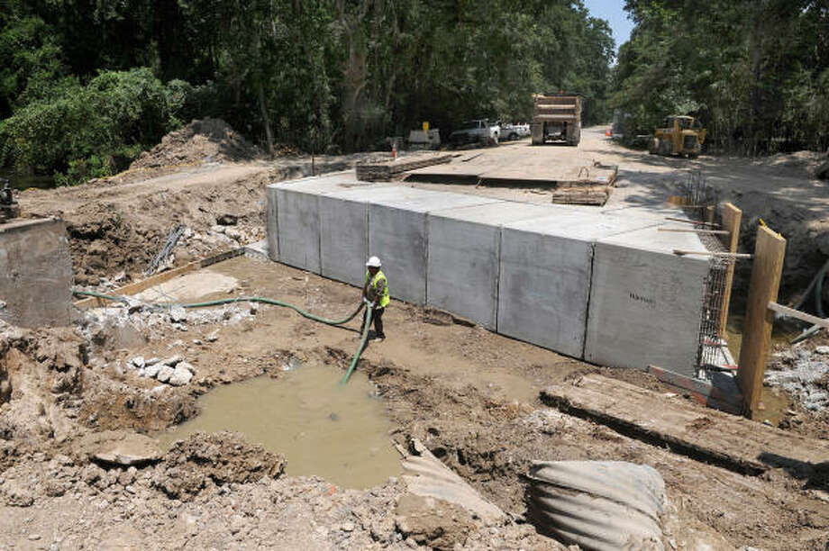 UNDER CONSTRUCTION: Members of the Houston Public Works crew continue their construction on the Kingwood Grove Park Bridge on June 26. Photo: Jerry Baker, For The Chronicle