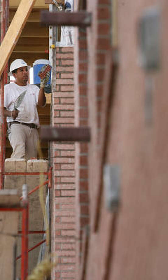A bricklayer works on the outside wall of the $39 million Camden Travis Street apartment complex, which is is one of the largest projects in the Midtown area. Photo: MAYRA BELTRAN :, CHRONICLE