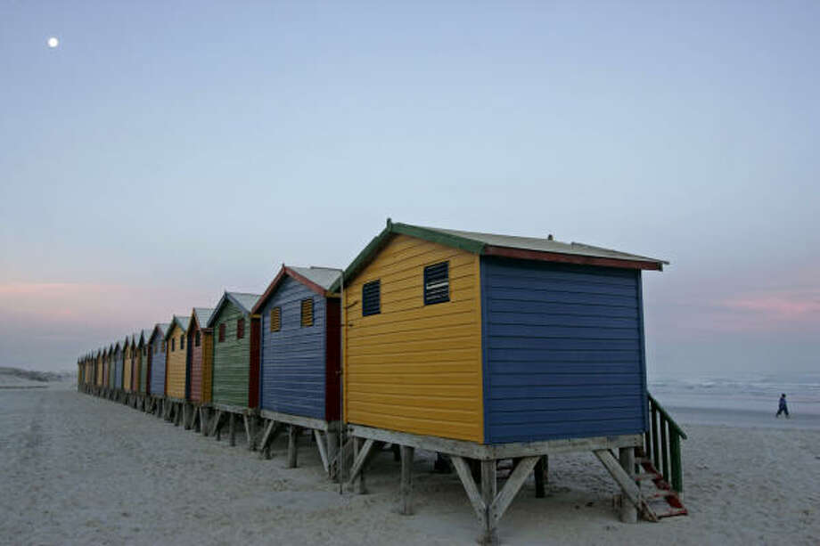 Multi-colored changing huts are seen as a man walks on the beach in Muizenberg, South Africa. Cape Town, the sparkling jewel in South Africa's tourist crown, regularly wins international travel awards. Photo: SCHALK VAN ZUYDAM, ASSOCIATED PRESS