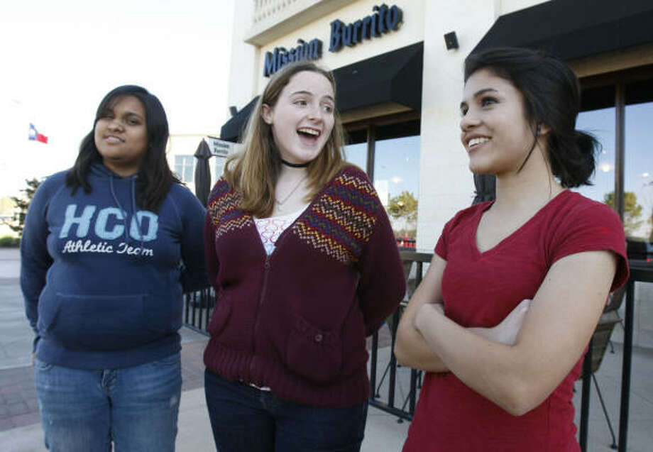 Cinco Ranch High students, from left, Nikita Shah, 17, Aubrey Morris, 15, and Maria Soto, 15, react to the news that counterfeit bills are also being passed in an elementary school. Katy ISD advised parents to give their children cash in small bills only, to pay online, or to use checks. Photo: Julio Cortez, Chronicle