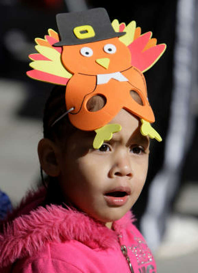 Gabriella Montelongo, 3, of Houston wears a turkey mask while watching the Thanksgiving parade today in downtown Houston. Photo: Melissa Phillip, Chronicle