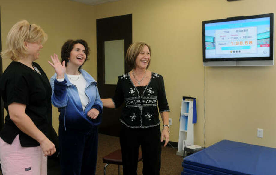 Dianne Helms, center, of Conroe, celebrates the end of her Wii workout during a therapy session with Mohna Zintgraff, right, a physical therapist for The Woodlands Specialized Therapy and Rehab Services, and occupational therapist Eva Howse-Wygand. Photo: Jerry Baker, For The Chronicle