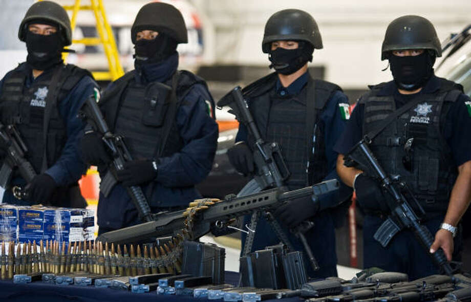 Weapons are displayed at a news conference with police in Mexico City. Mexican President Felipe Calderon has acknowledged the country's drug war is bloodier and tougher than he thought it would be. Photo: RONALDO SCHEMIDT, AFP/Getty Images