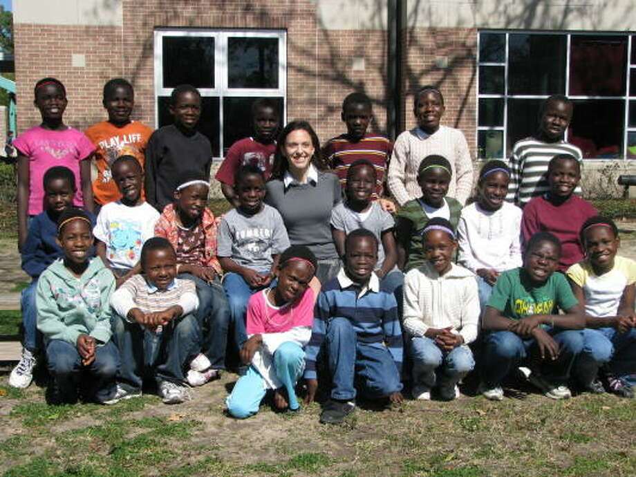 The African Children's Choir, pictured with Regis faculty member Emily Duncan, performed at the Regis School's international festival. Photo: Courtesy Of Awty