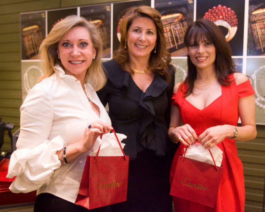 """Deborah Touchy, from left, Denise Antunes and Karina Barbieri beat the summer heat surrounded by the """"ice"""" on display in Cartier during a 100th anniversary celebration. Photo: Billy Smith II, Chronicle"""