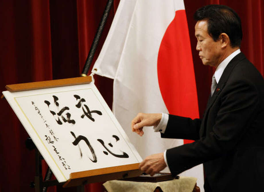 """Prime Minister Taro Aso checks his calligraphy of """"Reassurance and Energy."""" He's not alone with reading blunders. Photo: Koji Sasahara, AP"""