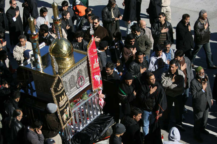 Muslims surround the replica of a shrine in Karbala, a tomb for Imam Hussein's brother Abbas, during the Ashura Procession in downtown Houston. The event commemorates the martyrdom of Hussein, the grandson of the prophet Muhammad, in 680 A.D.  Photo: Mayra Beltran, Chronicle