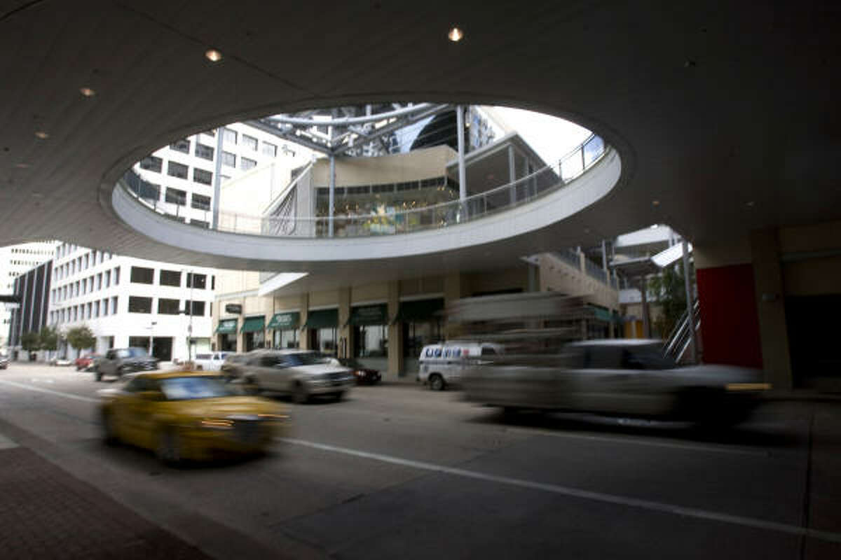 Cars drive under the Houston Pavilions center downtown Friday. Several retailers at the Pavilions say they are doing decent business.