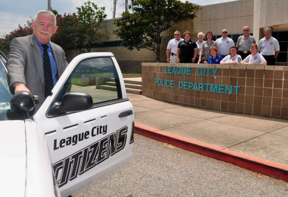 NEW PATROL FORCE: League City Police Chief Mike Jez stands by the vehicle that will be used by Citizens Patrol volunteers. Alumni of the city's Citizens Police Academy, background, are eligible to train to participate in the patrol. Photo: Jimmy Loyd, For The Chronicle