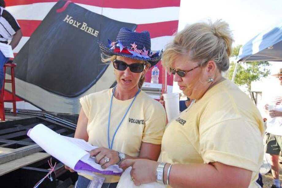 TEA PARTY: Jennifer Heiden, event chairperson, and Kris Winegar, event co-chair, compare notes at the Katy Tea Party Fourth of July Rally on July 4 north of Pattison in Waller County. Photo: Tony Bullard, For The Chronicle