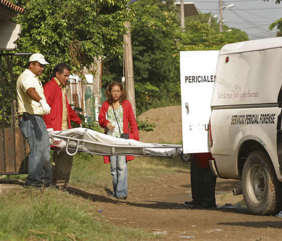 A body is removed from the police commander's house. Photo: Horacio Zamora, AP