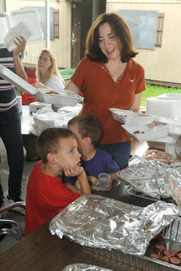 FEEDING THE FAMILY: Debbie Hennings, right, of Kingwood, mom to Nicholas, 5, left, and Andrew, 3, works her way through the serving line during the picnic. The event was held to raise funds to purchase new playground equipment for the school after a July 4 fire. Photo: Jerry Baker, For The Chronicle