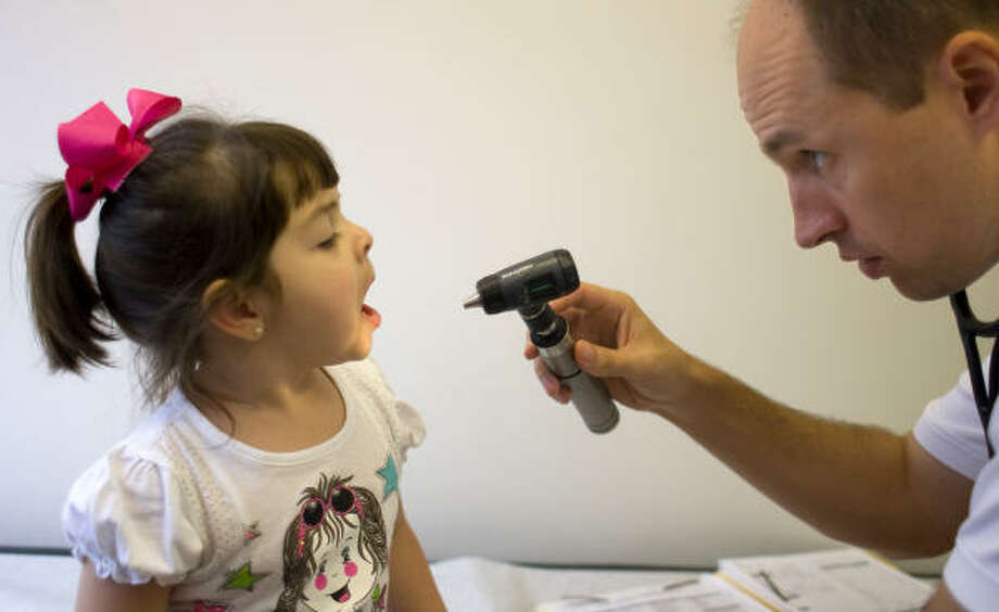 Olivia White, 2, of Pearland, showing signs of the flu, is examined by Dr. Matthew Wilber at the Texas Children's Pediatric Associates in Pearland.  Photo: Johnny Hanson, Chronicle
