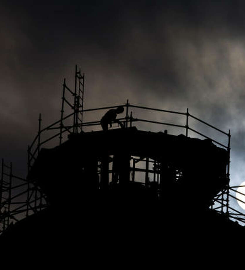Renovation of the dome of the Harris County 1910 Courthouse proceeded on Thursday, but today's expected downpours will likely cause a pause. Photo: Nick De La Torre, Chronicle