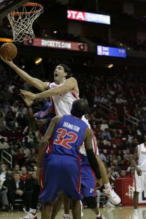 Rockets forward  Luis Scola drives to the basket while defended by Pistons guard Richard Hamilton. Photo: Billy Smith II, Chronicle