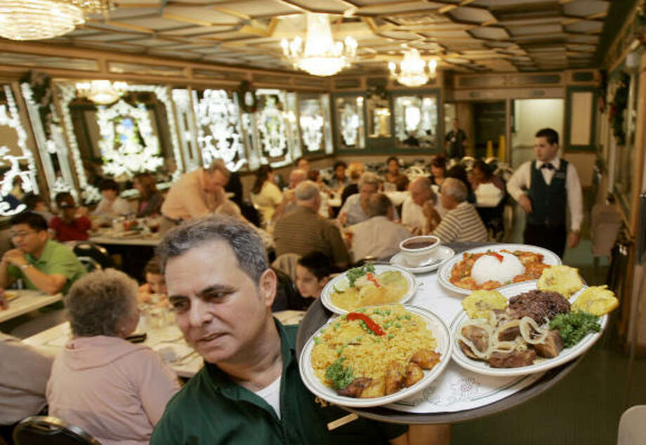 Enrique Martinez carries an order at the Versailles Restaurant in Miami's Little Havana neighborhood. Photo: Alan Diaz, Associated Press