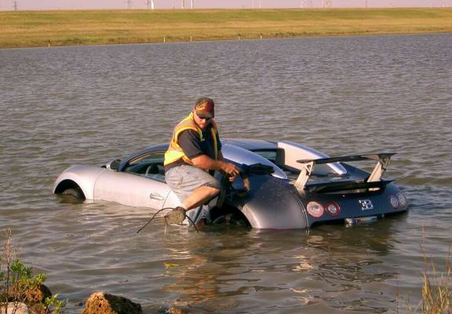Wrecker driver Gilbert Harrison prepares to retrieve a million-dollar Bugatti Veyron from the water in La Marque in 2009. The driver said he was startled by a pelican. Photo: Chris Paschenko, Galveston County Daily News