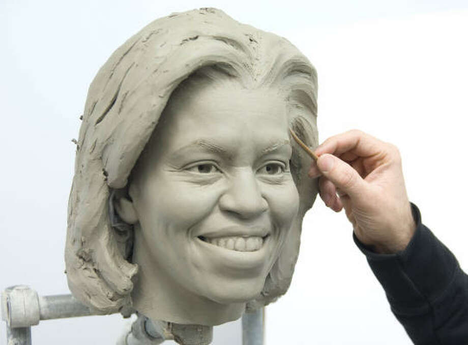 This image provided by Madame Tussauds shows senior sculptor Colin Jackson working on a clay head mold of first lady Michelle Obama at Merlin Studios in London. The clay molds are a crucial step in the up to six month-long figure creation process. The full wax figure of the new first lady is expected to be unveiled at Madame Tussauds in Washington in March. Photo: Merlin Studios, AP