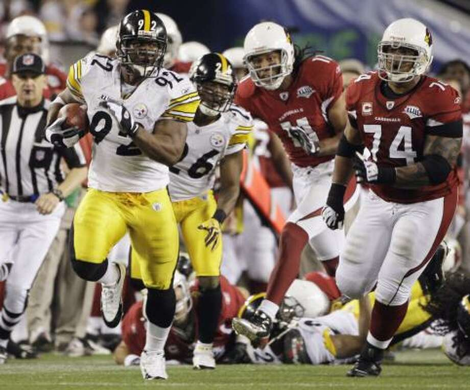 James Harrison (92) takes a Kurt Warner pass the length of the field on the last play of the first half to give the Steelers a 17-7 lead at the break. It was the longest play in Super Bowl history. Photo: Mark Humphrey, AP