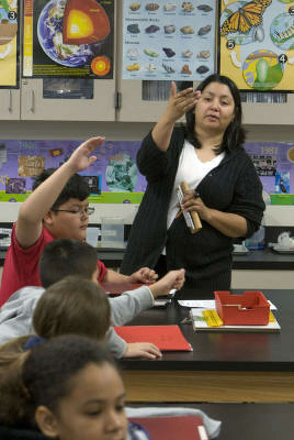 Teacher Norma Martinez leads students through a science lab at HISD's Cornelius Elementary last month. The fifth-graders were studying how blubber interacts with water of different temperatures. The magnet school has a lab teacher for each grade.