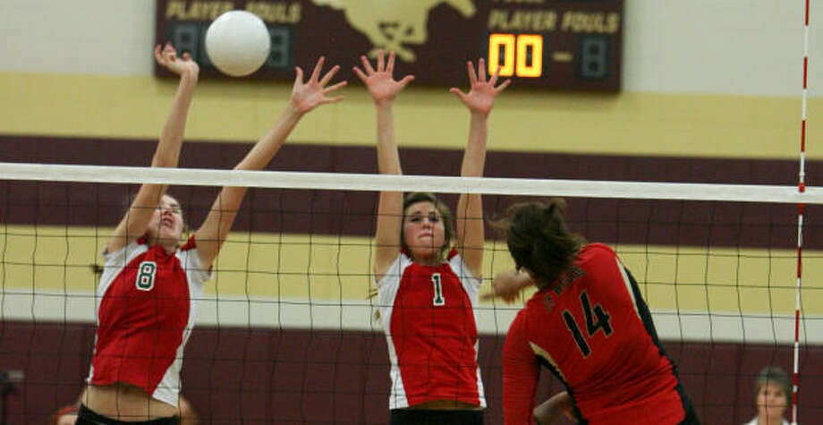 Cy Woods' Desiree Elliott (14) spikes the ball as The Woodlands' (l-r) Katie Messing and Emily Phillips attempt to block. Photo: Billy Smith II, Chronicle
