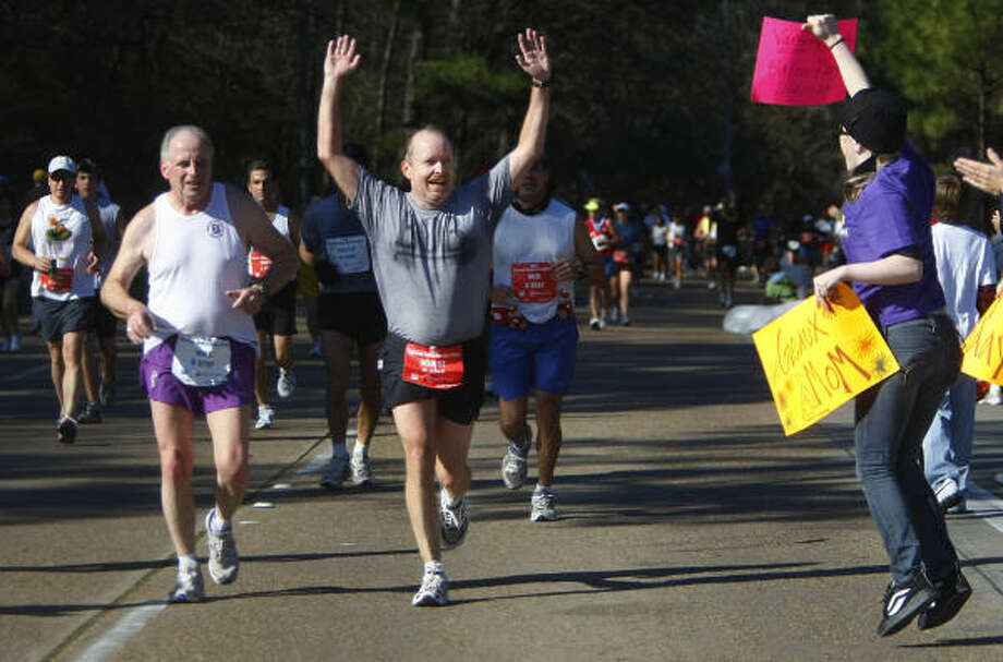 ROADSIDE SUPPORT: Robert Thompson greets Robbi Lewis who cheers for him near the 22 mile maker along Memorial during the Chevron Houston Marathon last year. Photo: Mayra Beltran, Chronicle