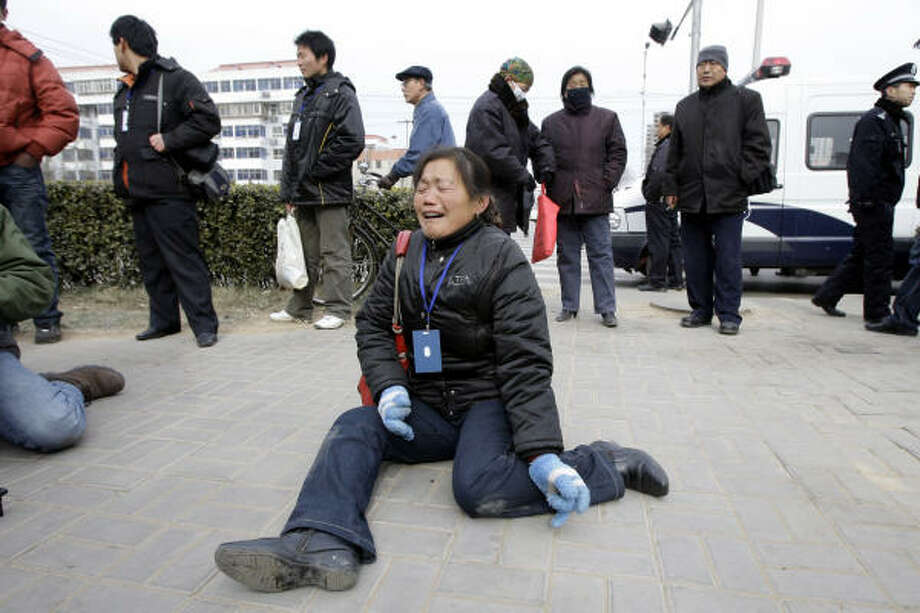 Zheng Shuzhen, center, the grandmother of a baby who died after drinking tainted milk, cries outside the Intermediate People's Court in Shijiazhuang, in China's Hebei province today. Photo: Greg Baker, AP