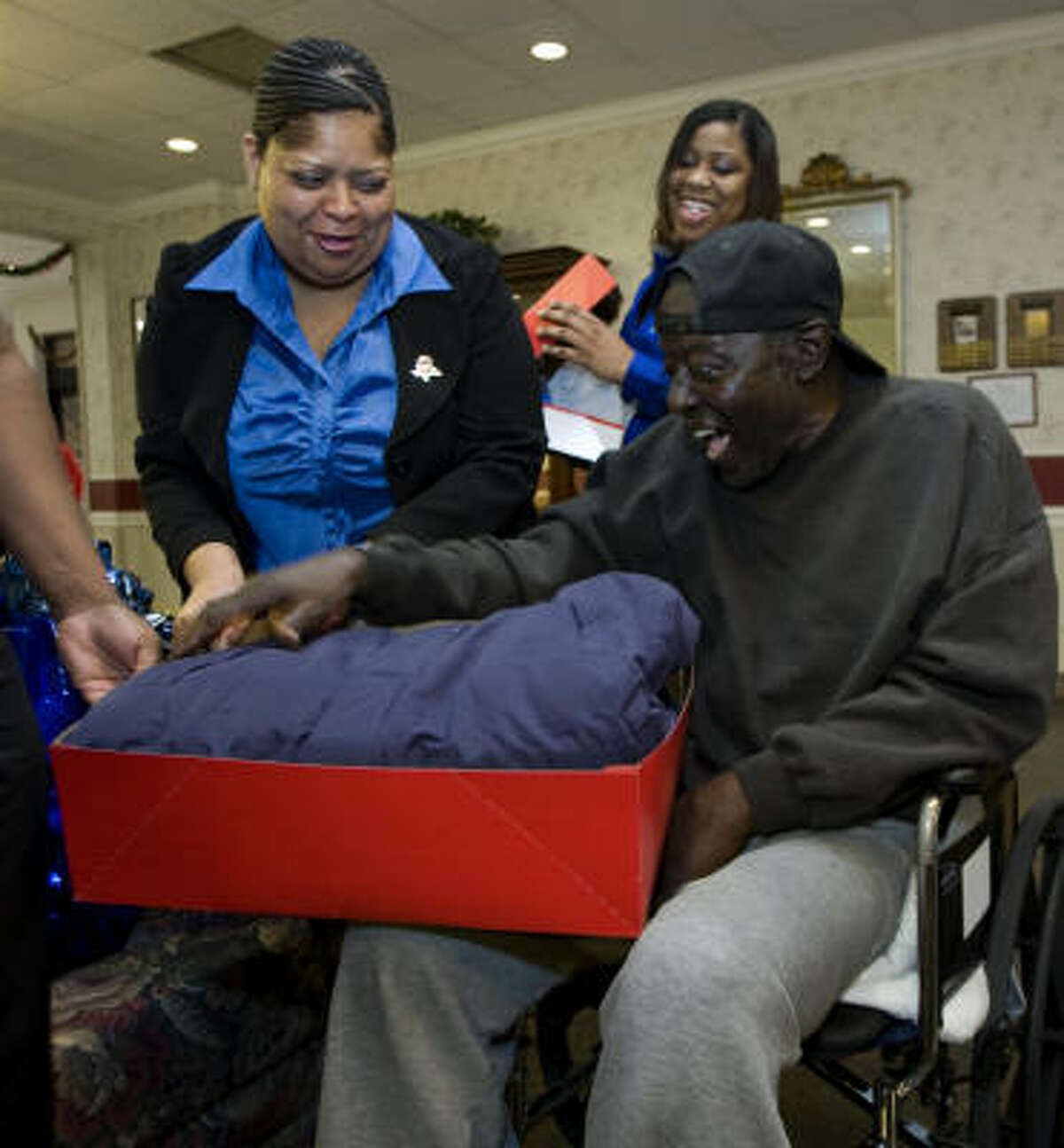 Samuel Reed, one of about 1,400 adult wards of the state in Harris County, is excited to receive a coat from Vanessa Shippard, left, and Shanna Battle on Thursday.