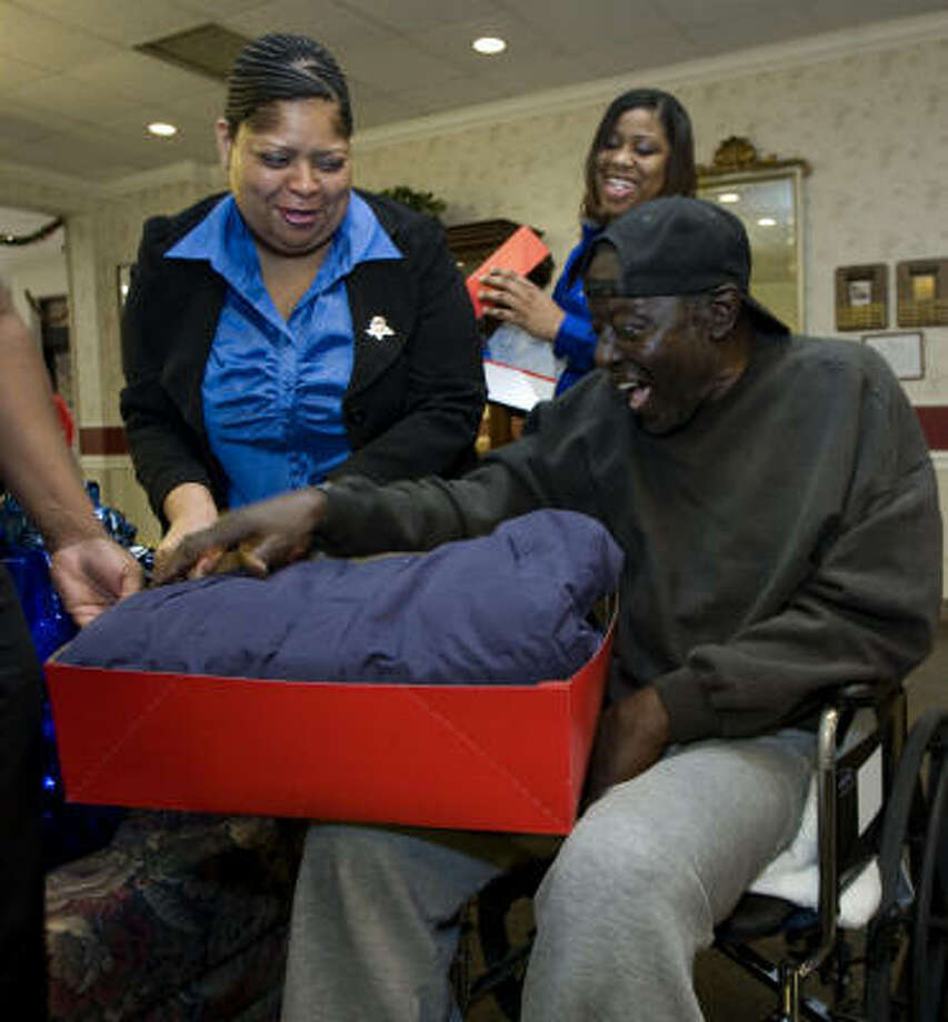 Samuel Reed, one of about 1,400 adult wards of the state in Harris County, is excited to receive a coat from Vanessa Shippard, left, and Shanna Battle on Thursday. Photo: Brett Coomer, Chronicle