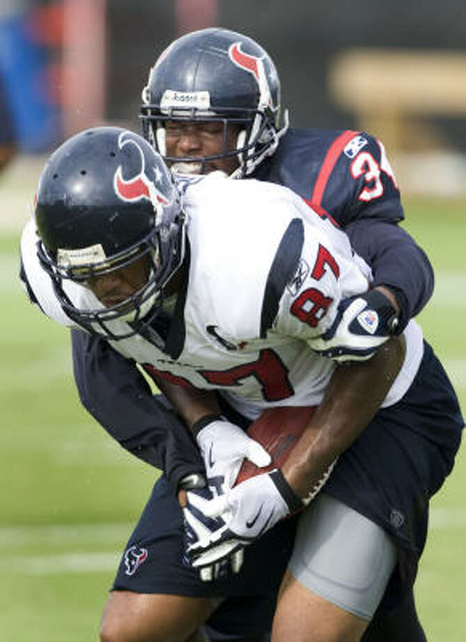 Anthony Hill, shown in front of Texans safety Dominque Barber, is one of four tight ends competing for a roster spot. Photo: Brett Coomer, Chronicle
