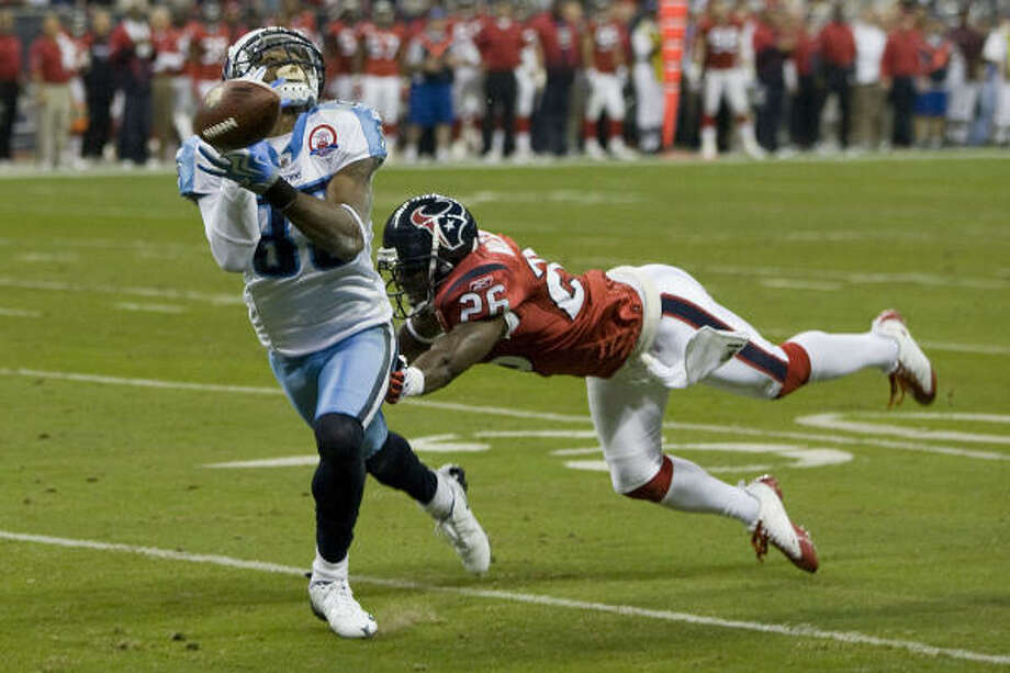 Texans safety Eugene Wilson, breaking up a pass intended for the Titans' Nate Washington on Monday, will likely miss the rest of the season. Photo: Brett Coomer, Chronicle