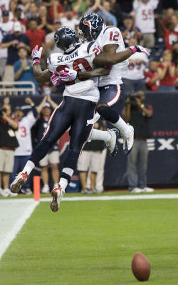 Texans running back Steve Slaton (20) got sky-high with teammate Jacoby Jones to celebrate Slaton's 32-yard touchdown run in the second quarter Sunday. Photo: Brett Coomer, Chronicle