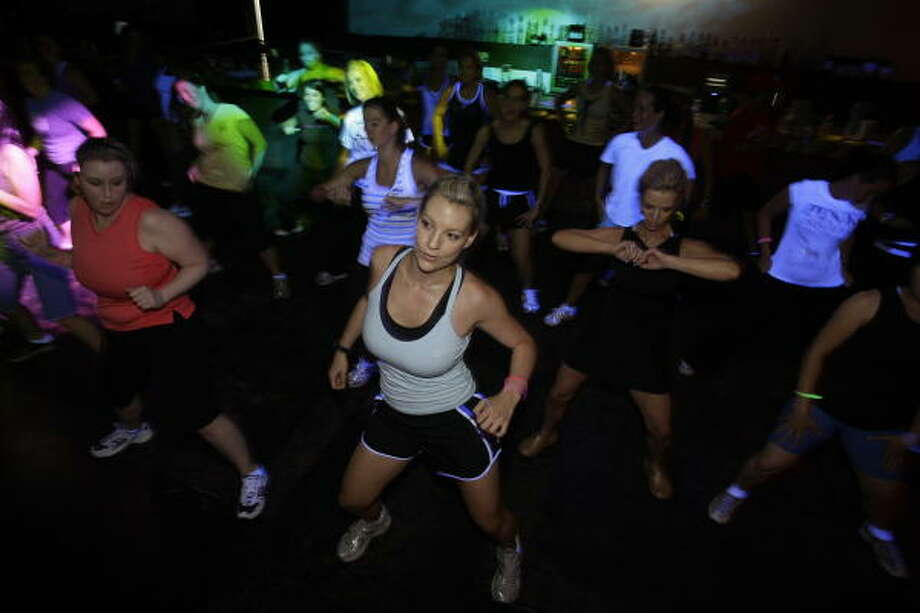 Melissa Wozny of Houston, center, works out with a group at Nightclub Cardio, a class at Pravada nightclub that mixes dance and aerobics. Photo: Melissa Phillip, Chronicle