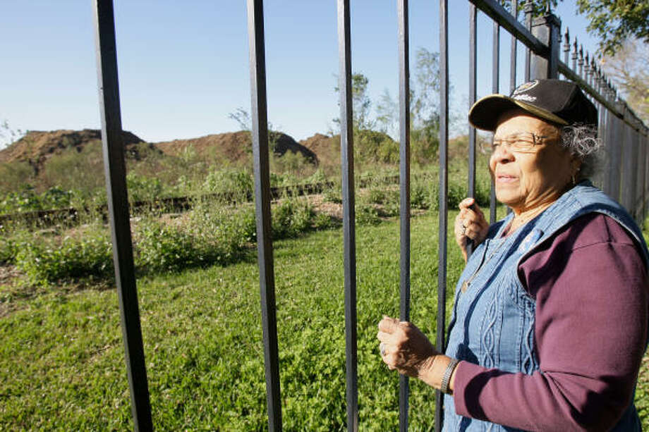Martha Solomon looks at mountains of mulch piled in a lot near her back yard Tuesday. Photo: Melissa Phillip  , Chronicle